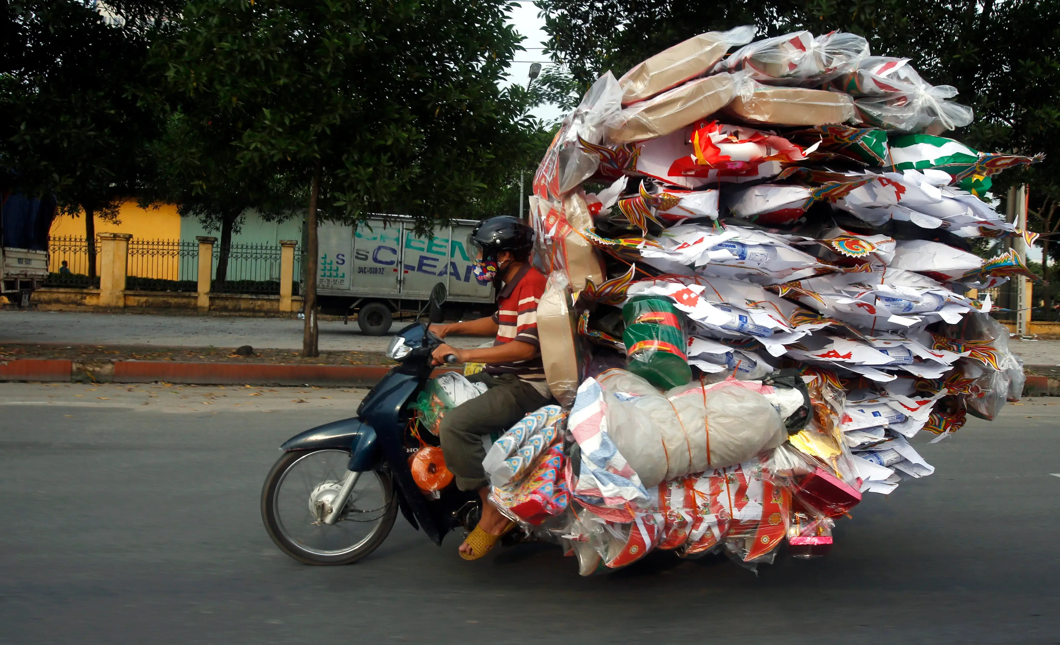 A man transports paper replicas of various items to be sold for the Vu Lan Festival (