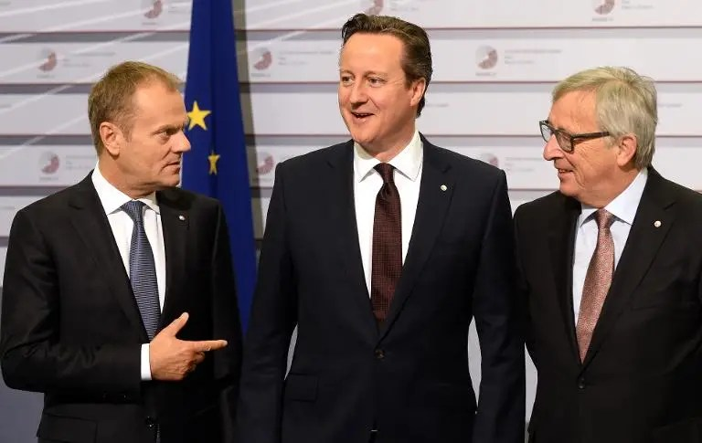 British Prime Minister David Cameron (C) is welcomed by European Commission president Jean-Claude Juncker (R) and European Council president Donald Tusk on the second day of the European Union eastern partnership summit in Riga, on May 22, 2015