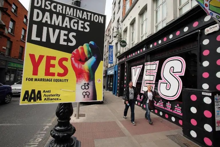 Pedestrians walk past signs in favour of same-sex marriages in Dublin on May 21, 2015