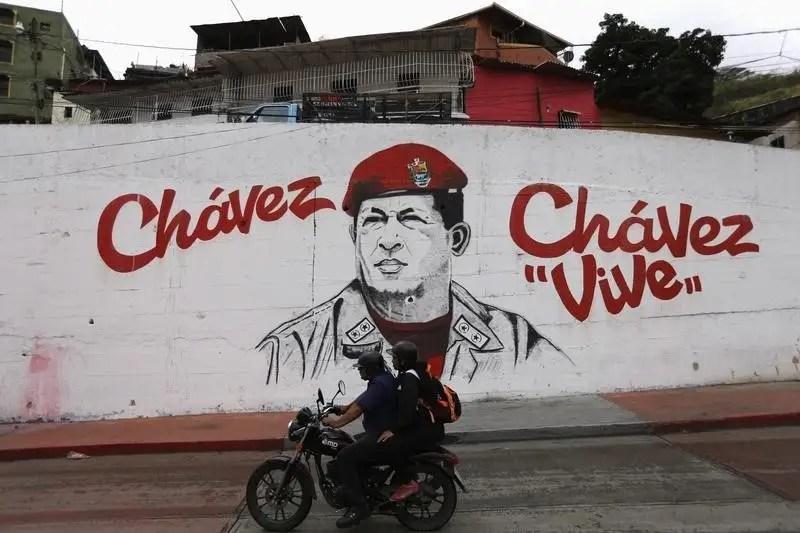 A motorcycle rides past a mural depicting late Venezuelan President Hugo Chavez, near his mausoleum in Caracas March 5, 2015. REUTERS/Jorge Silva