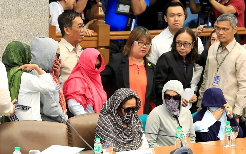 Relatives of slain people cover their faces as they attend a Senate hearing investigating drug-related killings at the Senate headquarters in Pasay city, metro Manila, Philippines August 22, 2016. REUTERS/Romeo Ranoco