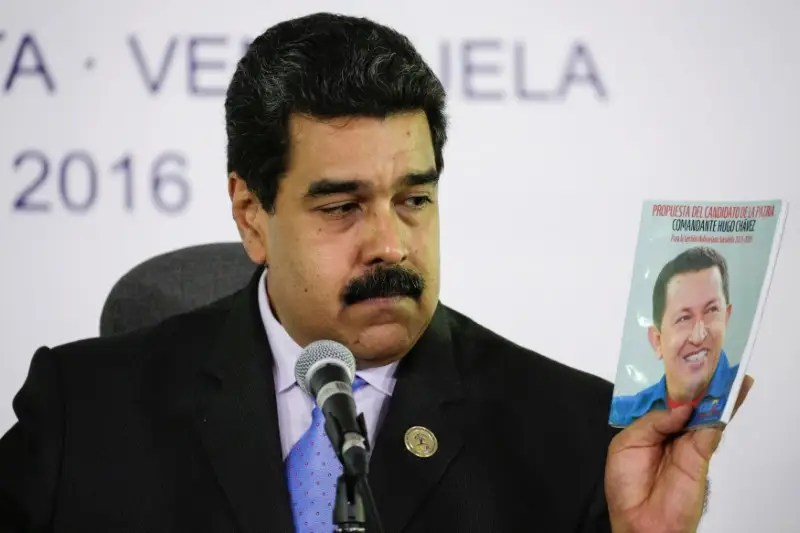 Venezuela's President Nicolas Maduro holds a book with a photo of Venezuela's late President Hugo Chavez as he talks to the media during a news conference after the 17th Non-Aligned Summit in Porlamar, Venezuela September 18, 2016. REUTERS/Marco Bello