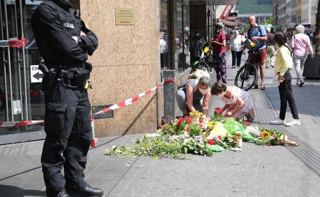 Two people leave flowers on the street in Würzburg where one of the murdered women was attacked on Friday.