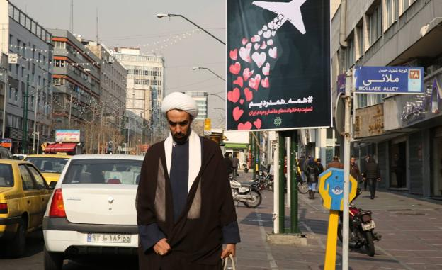 An Iranian cleric passes in front of a tribute sign.