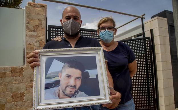 Adán Rodríguez and Nany García hold a photo of Juan Manuel at the door of his house.