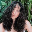 Debora Nascimento mantém o cabelo cacheado longo e com uma franja ondulada e quase sem volume