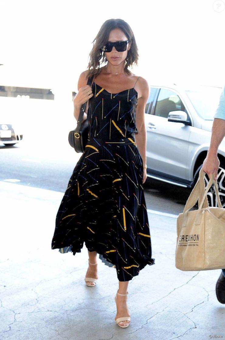 Victoria Beckham à l'aéroport LAX à Los Angeles, porte un haut et une jupe plissée Victoria Beckham (pré-collection automne-hiver 2016), un sac Victoria Beckham (modèle Half Moon) et des sandales beiges. Le 1er août 2016.