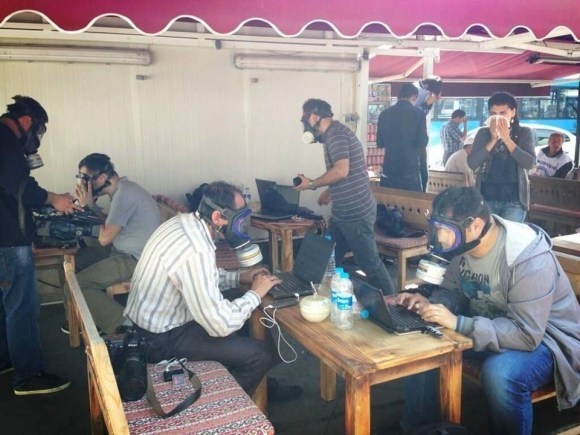 Turkish journalists wearing gas masks as they write their stories on their laptops. Link The Economist explains what's going on in Turkey.