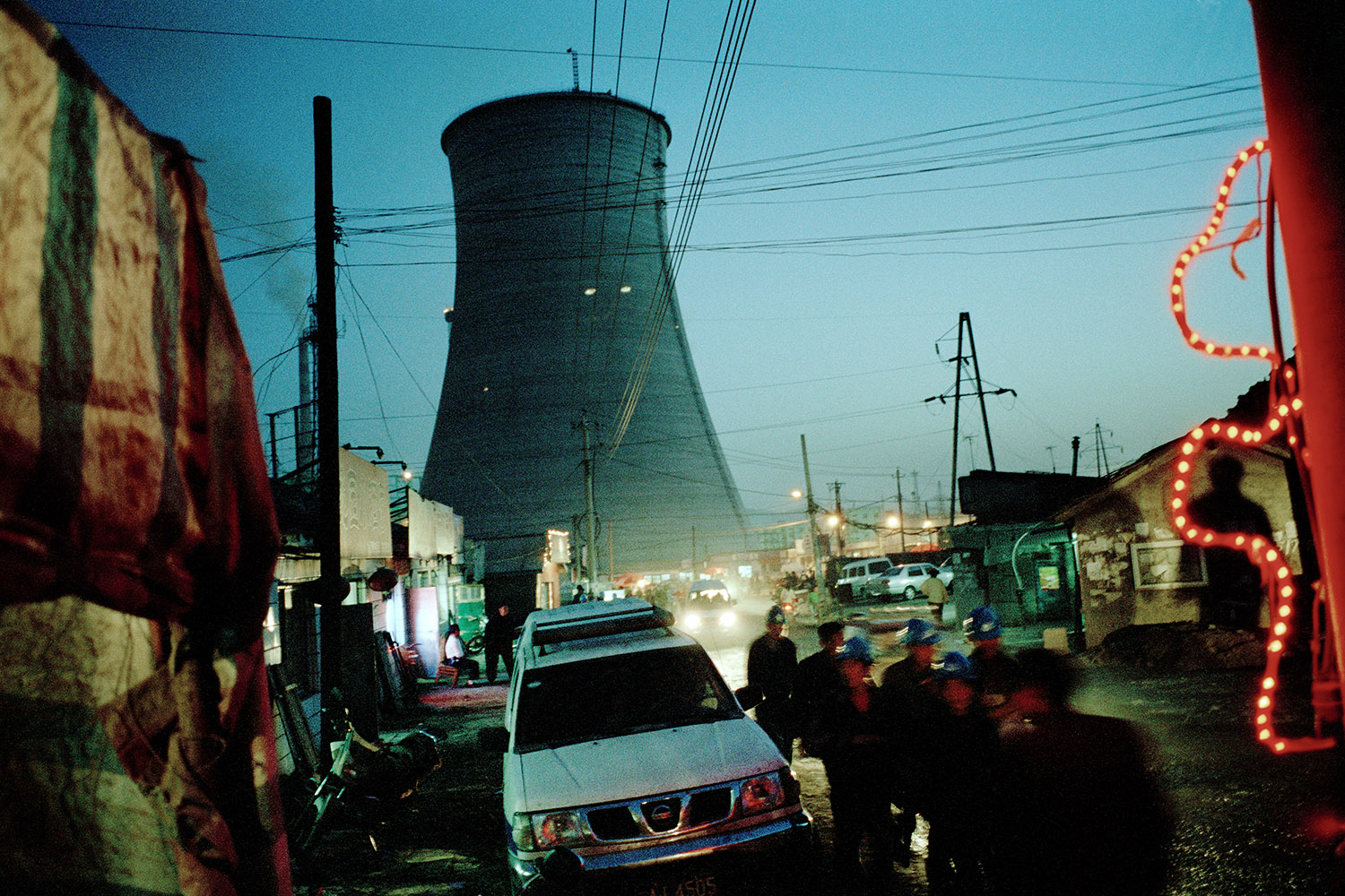 Workers return home after a days work at a nearby coal power station and steel plant. Behind in the distance is a new cooling tower that has just been erected, the station is increasing its capacity. Tonghua, China.