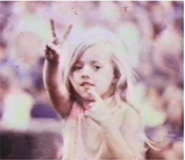 Child gives peace sign during Goose Lake International Music Festival. Photo: Goose Lake Film Still.