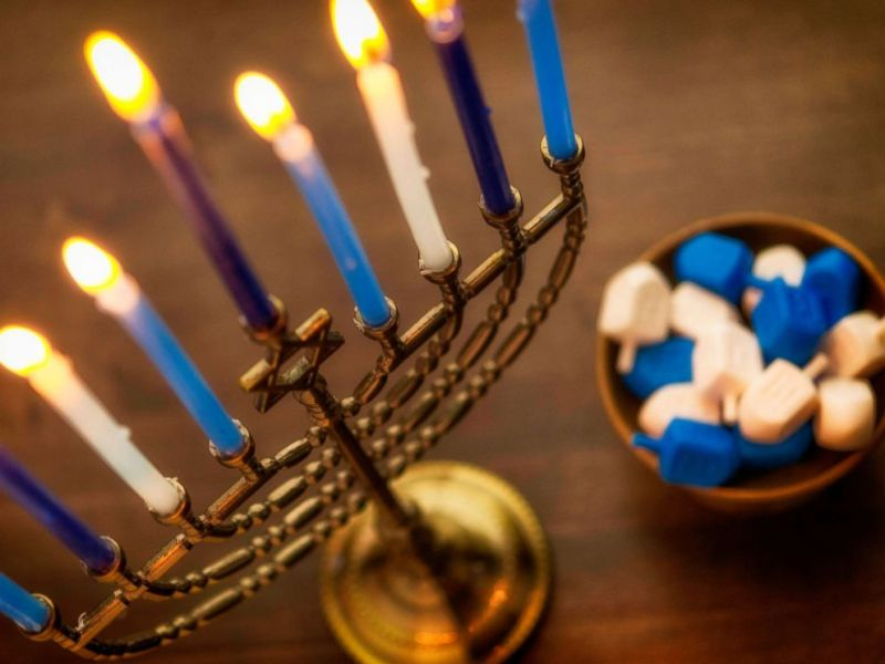Menorah with burning candles and dreidel. What you need to know about Hanukkah By LINDSEY JACOBSON. Nov 27, 2018, 11:21 AM ET
