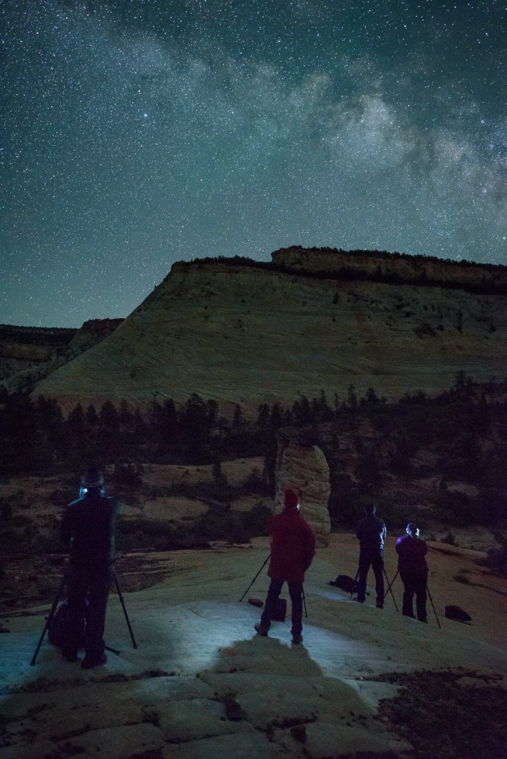 Workshop students in Zion National Park. This view of Checkerboard Mesa faces southeast, and shows movement in the stars that would be visible only in a very large print, or when pixel-peeping at 100 percent magnification. Nikon D750, Nikkor 24mm f/1.4 lens. 15 seconds, f/f2.8, ISO 12800.