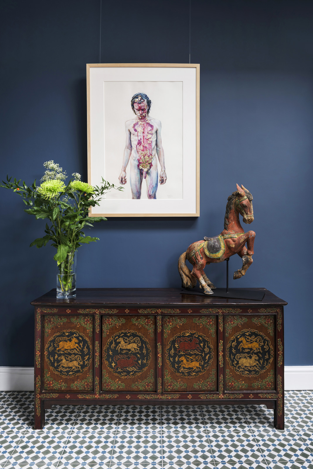 A painting by Daniel Barkley, displayed over a Tibetan Chest and an antique Burmese horse.