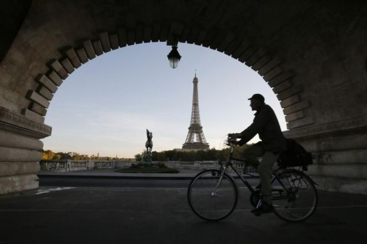 699815-a-man-takes-an-early-morning-bicycle-ride-across-a-bridge-near-the-eiffel-tower-in-paris.jpg