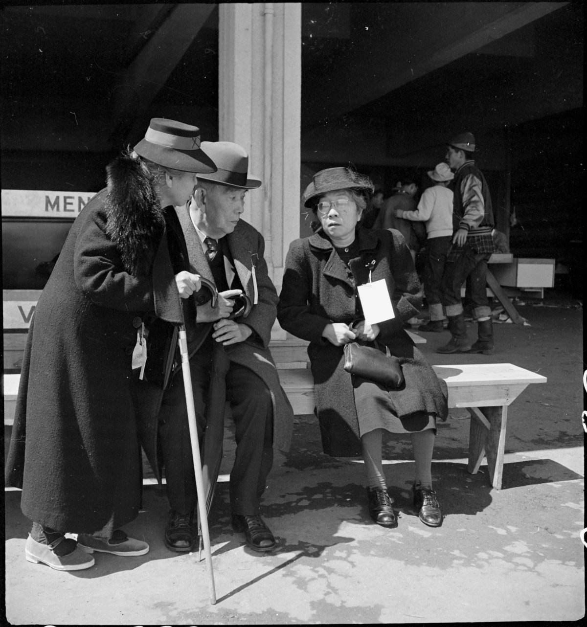 San Bruno, Caliofnira. These older evacuees of Japanese ancestry have just been registered and are resting before being assigned to their living quarters in the barracks. The large tag worn by the woman on the right indicates special consideration for aged or infirm.