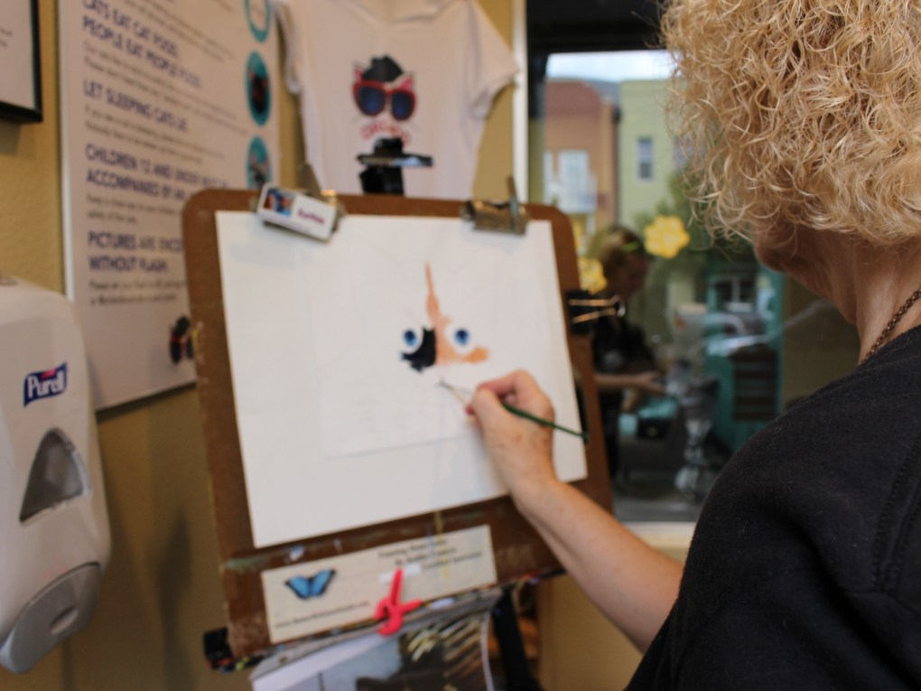 "Local artist Kathie Camara paints a picture of a kitten during the grand opening of the Orlando Cat Cafe Thursday. Camara. Placed between the cat playroom and the Axum Coffee shop, guests watched her paint, as well as see some of her typical ""pet art."""