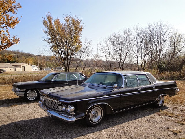 two old black station wagons in a field