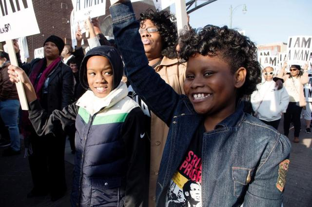 """Lashundra Richmond stands behind her son Phillip and her goddaughter Madison as they hold up """"I AM A MAN"""" signs during the reenactment of the famous Withers photograph.  CREDIT PHOTO BY SYDNEY MATZKO"""