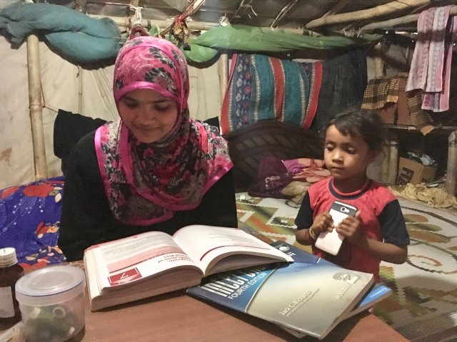 Tasmida studying in her room with her younger relative looking on.