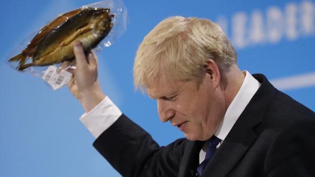 Boris Johnson muestra un arenque empaquetado este miércoles en un acto de la carrera por el liderazgo conservador