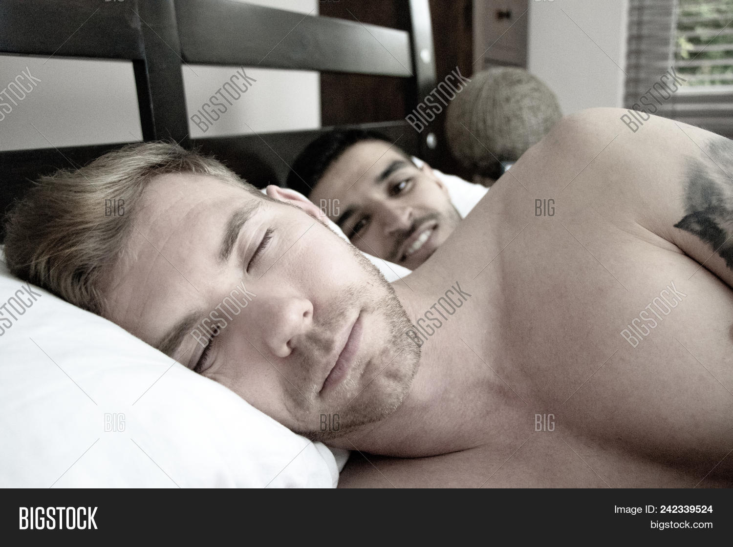 Two Handsome Gay Men In Bed Together One Is Sleeping As The Other Watches