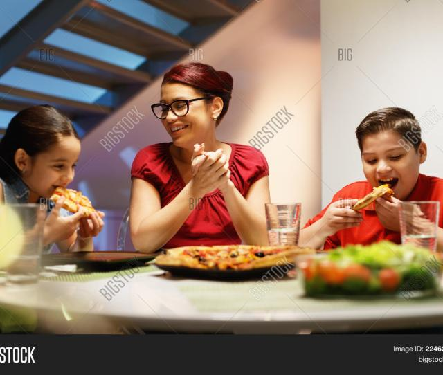 Hispanic Family With Mom Son And Daughter Having Dinner At Home And Eating Homemade Pizza