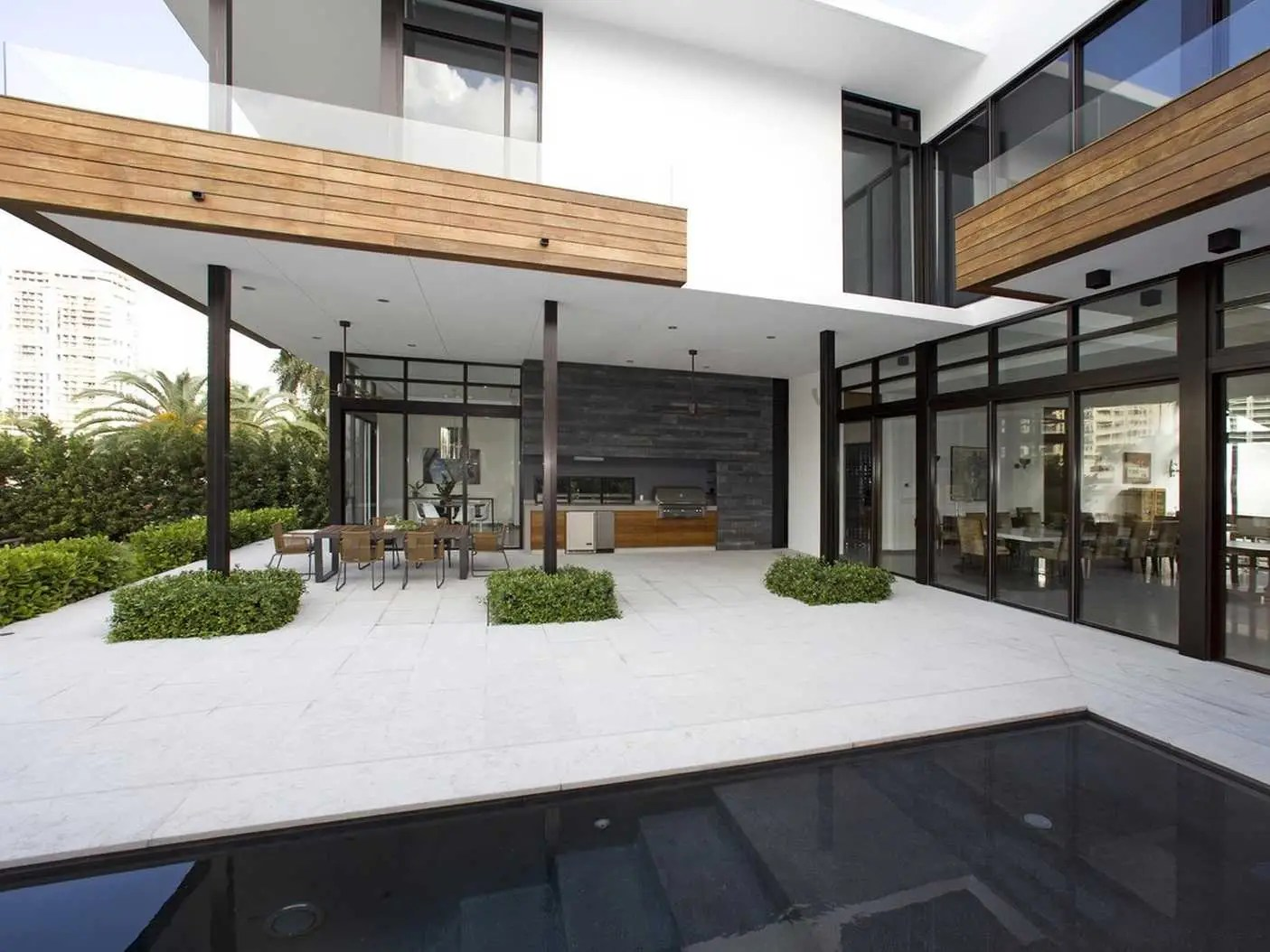 On the waterfront side of the home, there is an infinity-edge pool, barbecue grill, bar, and covered seating area.