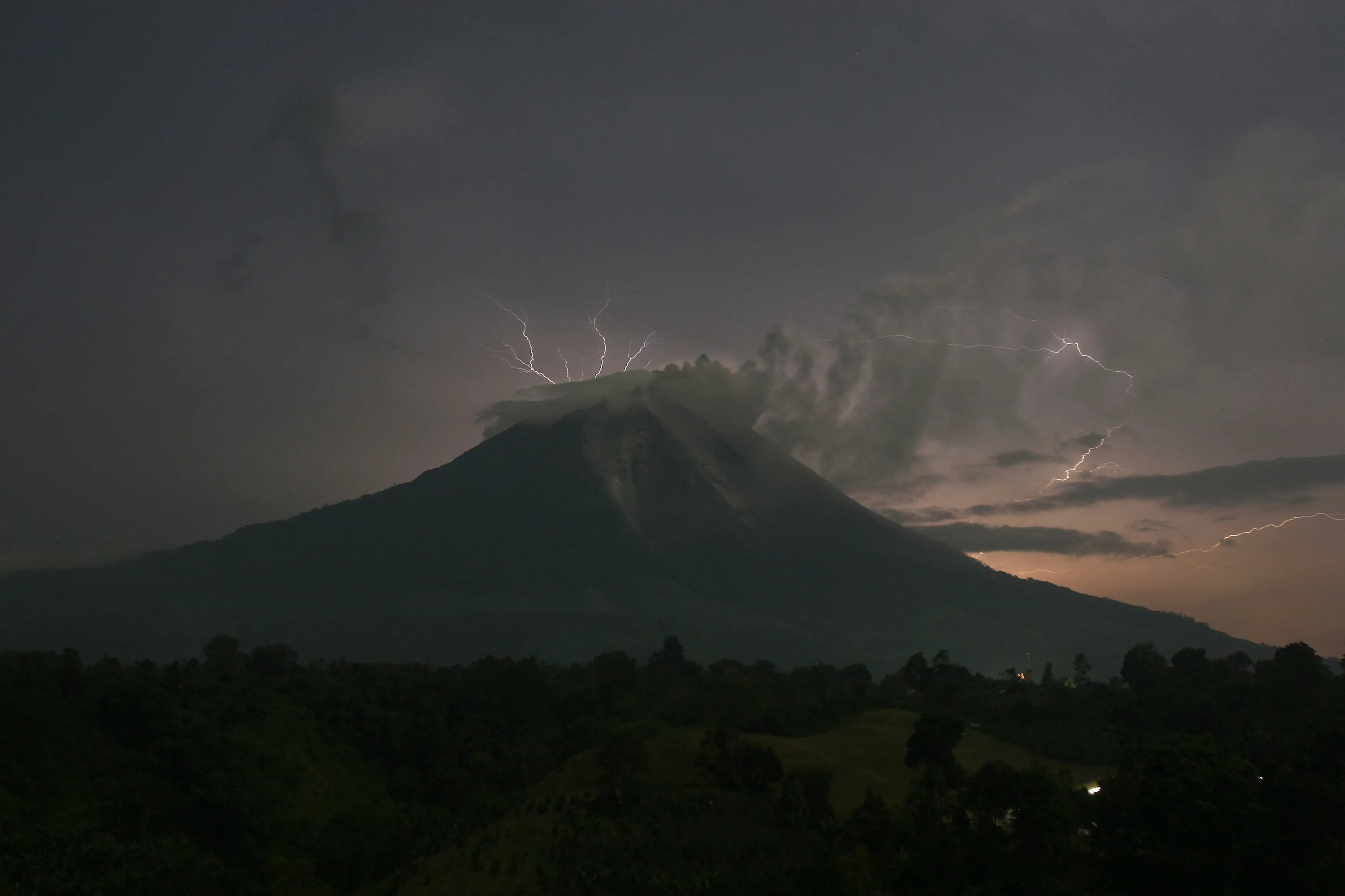 Lightning strikes as Indonesia's Mount Sinabung volcano spews ash and hot lava.