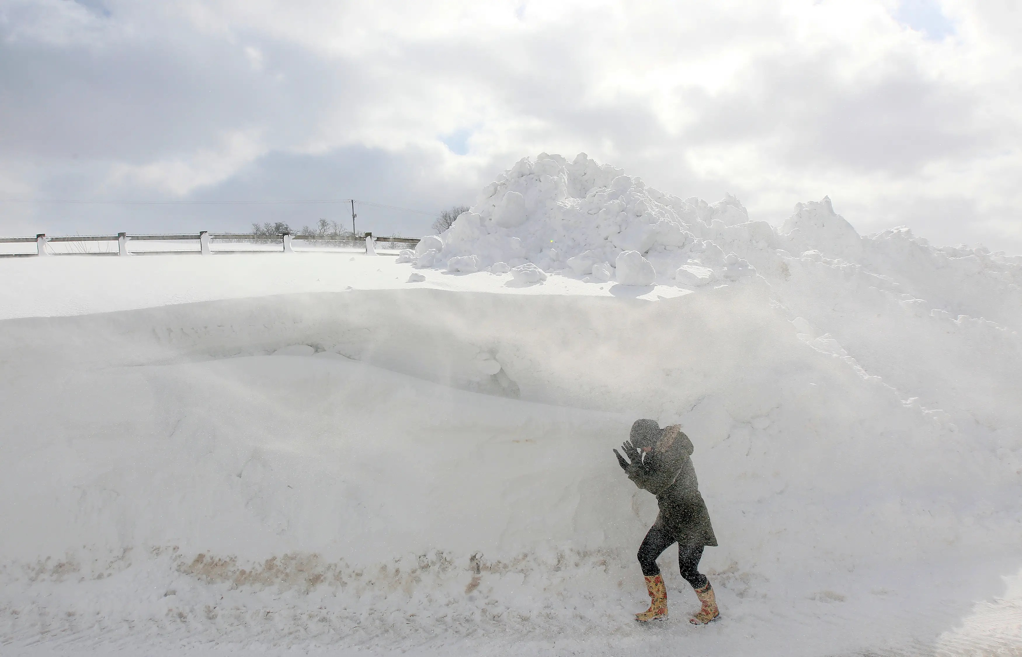 A person walks past a snowdrift in Northern Ireland.