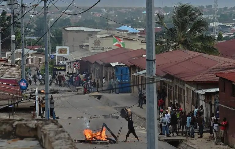 A protestor opposed to the Burundian president's third term throws material onto a burning barricade in the Kinanira neighborhood of Bujumbura on May 21, 2015