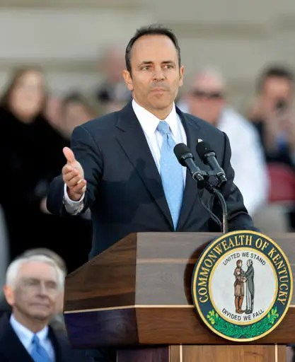 FILE - In this Dec. 8, 2015, file photo, Kentucky Gov. Matt Bevin gives his inaugural address as former Kentucky Gov. Steve Beshear, lower left, listens on the steps of the State Capitol in Frankfort, Ky. Kentucky's two most recent governors are feuding and have verbally attacked each other more than any other governors in recent memory. (AP Photo/Timothy D. Easley, File)