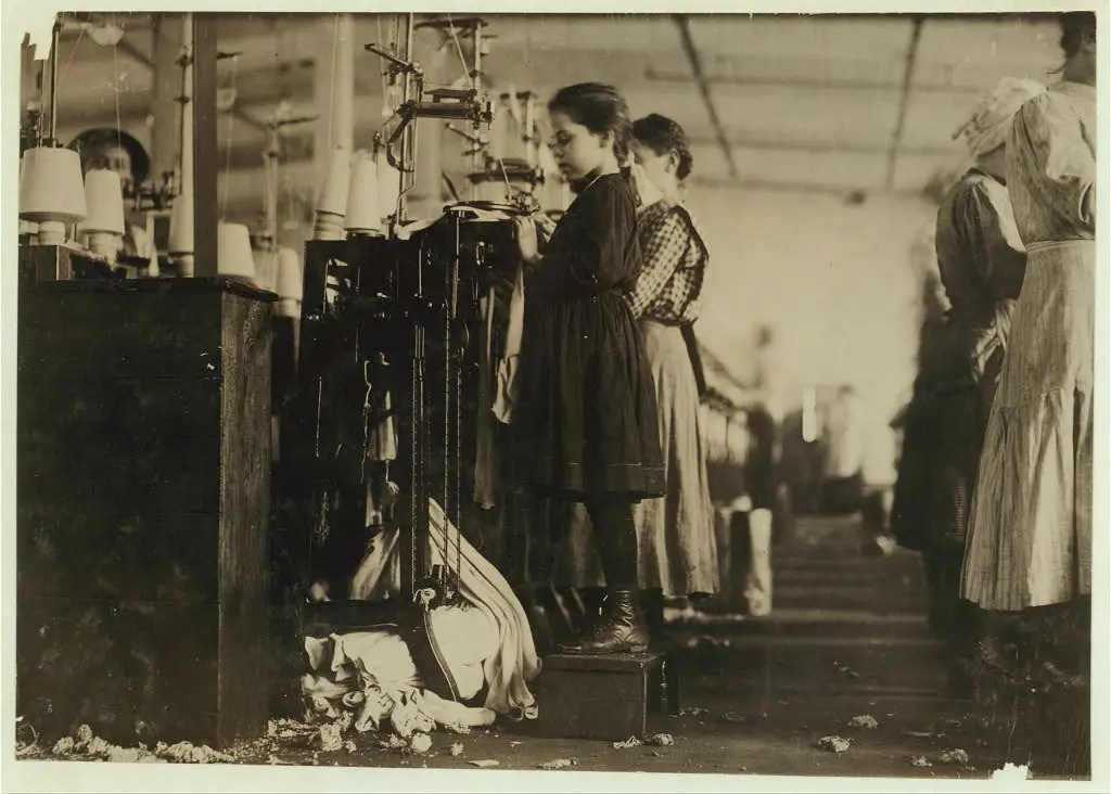 This little girl, like many others in this state, is so small she has to stand on a box to reach her machine. She is regularly employed as a knitter in a hosiery mill. Said she did not know how long she had worked there. Location: Loudon, Tennessee, December 1910.