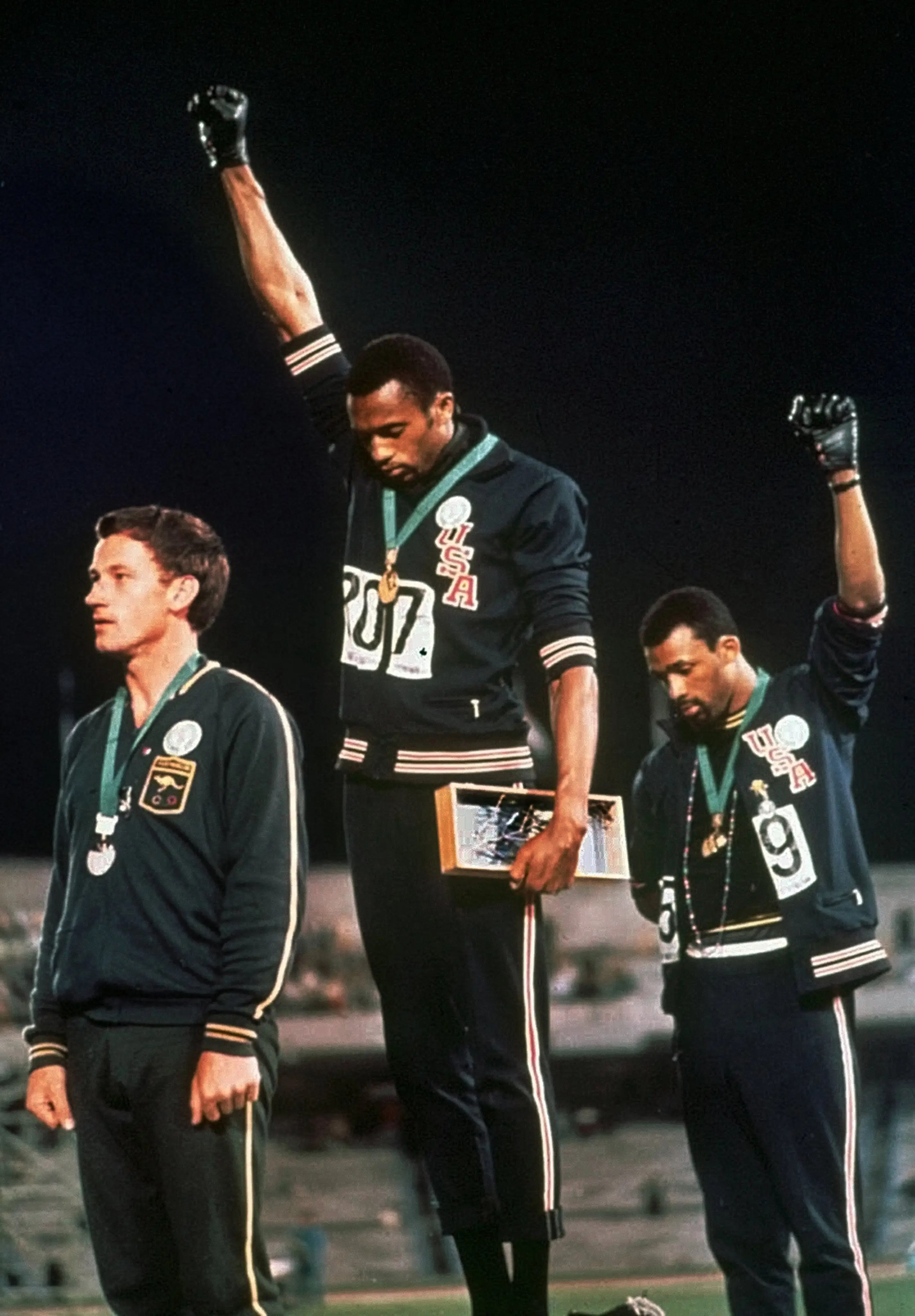 """Mexico, 1968: While on the podium, US medal winners Tommie Smith and John Carlos raised their fists in silent protest against the continued racial discrimination against black people in the US. They were booed by many people in the crowd and the International Olympic Committee condemned their actions, calling it """"a deliberate and violent breach of the fundamental principles of the Olympic spirit."""""""