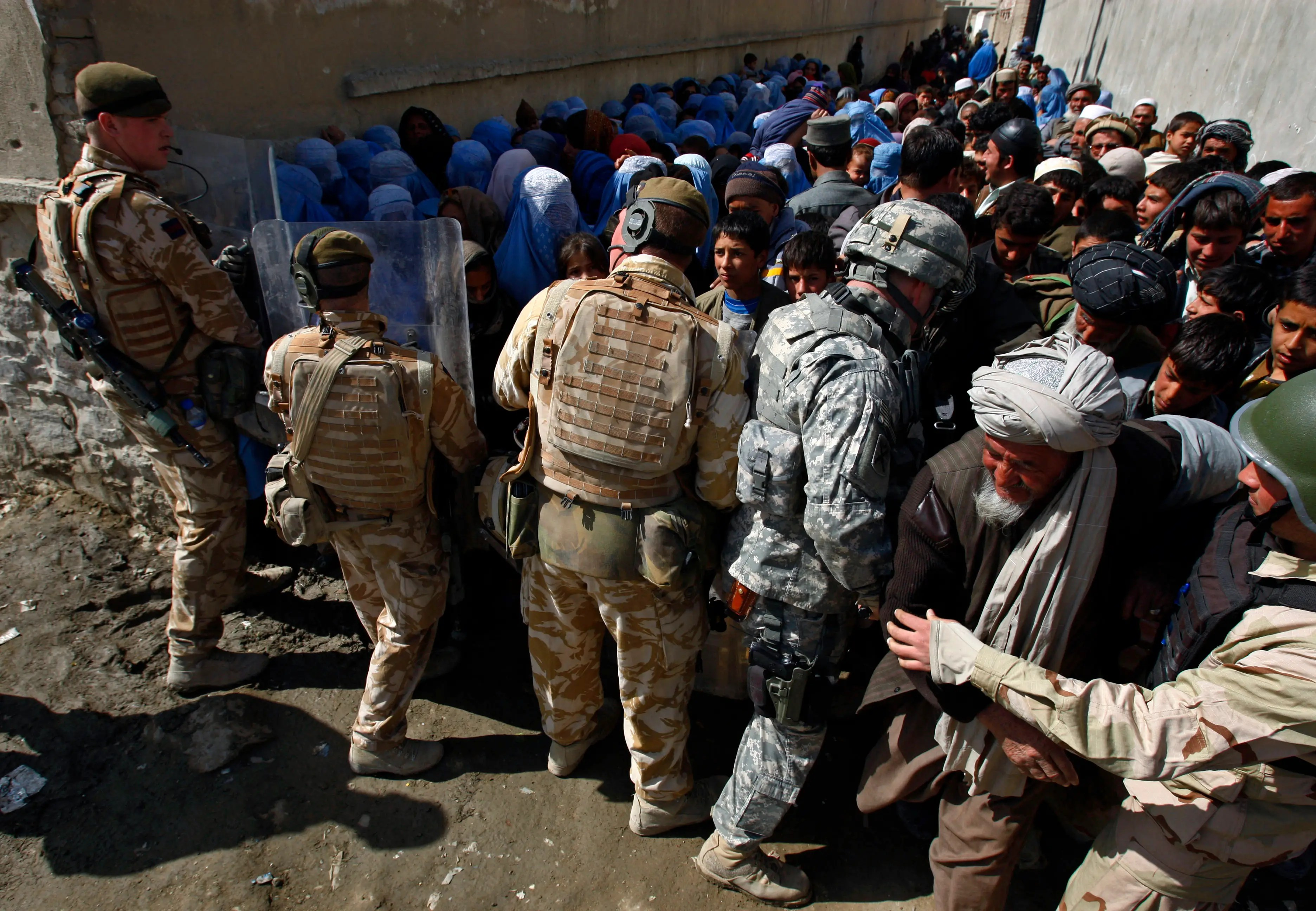 British and US soldiers control the crowd during medical assistance in Kabul, February 26, 2008.