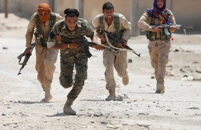 Kurdish fighters from the People's Protection Units (YPG) run across a street in Raqqa, Syria July 3, 2017. REUTERS/Goran Tomasevic