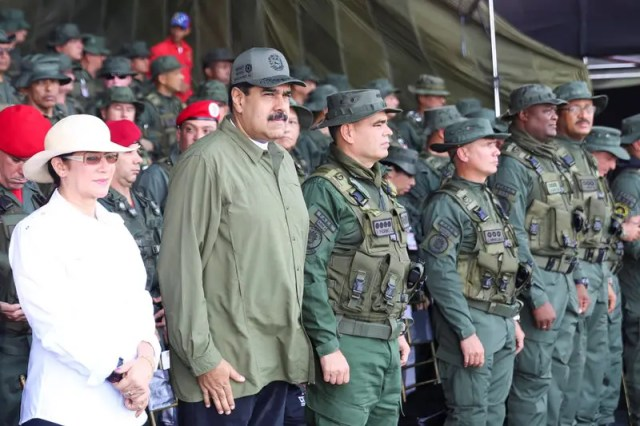 Venezuela's President Nicolas Maduro (2nd L) attends a military parade, as he is flanked by his wife Cilia Flores (L) and Venezuela's Defence Minister Vladimir Padrino Lopez (C), in Maracay, Venezuela September 26, 2017. Miraflores Palace/Handout via REUTERS