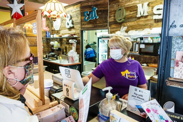 Florida, Brooksville, Main Street Eatery, cashier and customer wearing face masks during Pandemic.