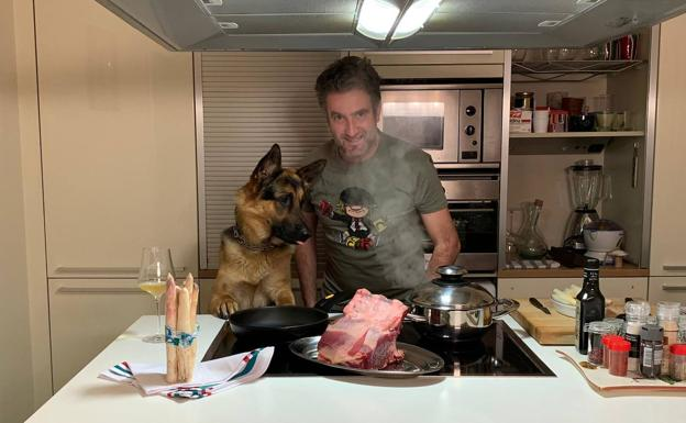 Josean Alija posa en su cocina junto a su perro.