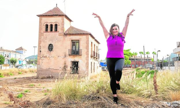 Delfina Roca, in a dancing position, next to the Casa de la Tía Belmonta, an abandoned architectural gem in the district of Cobatillas.