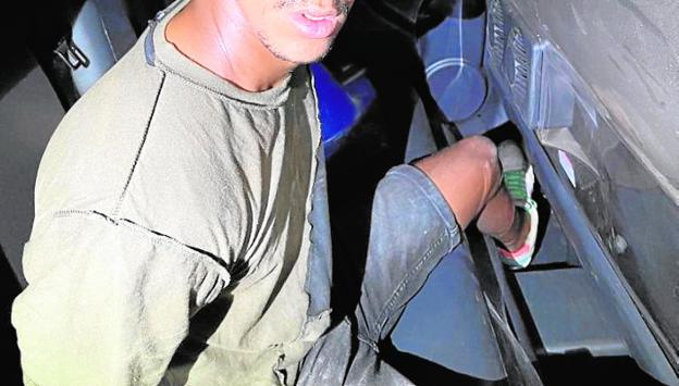 The suspect, detained inside a police vehicle.