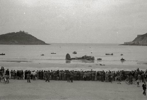 Avión de Degrelle, tras estrellarse en La Concha, con cientos de vecinos de San Sebastián observando la escena