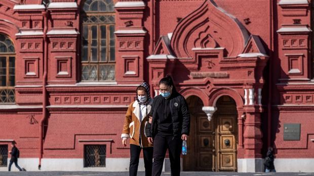 Dos mujeres caminan con mascarillas por Moscú