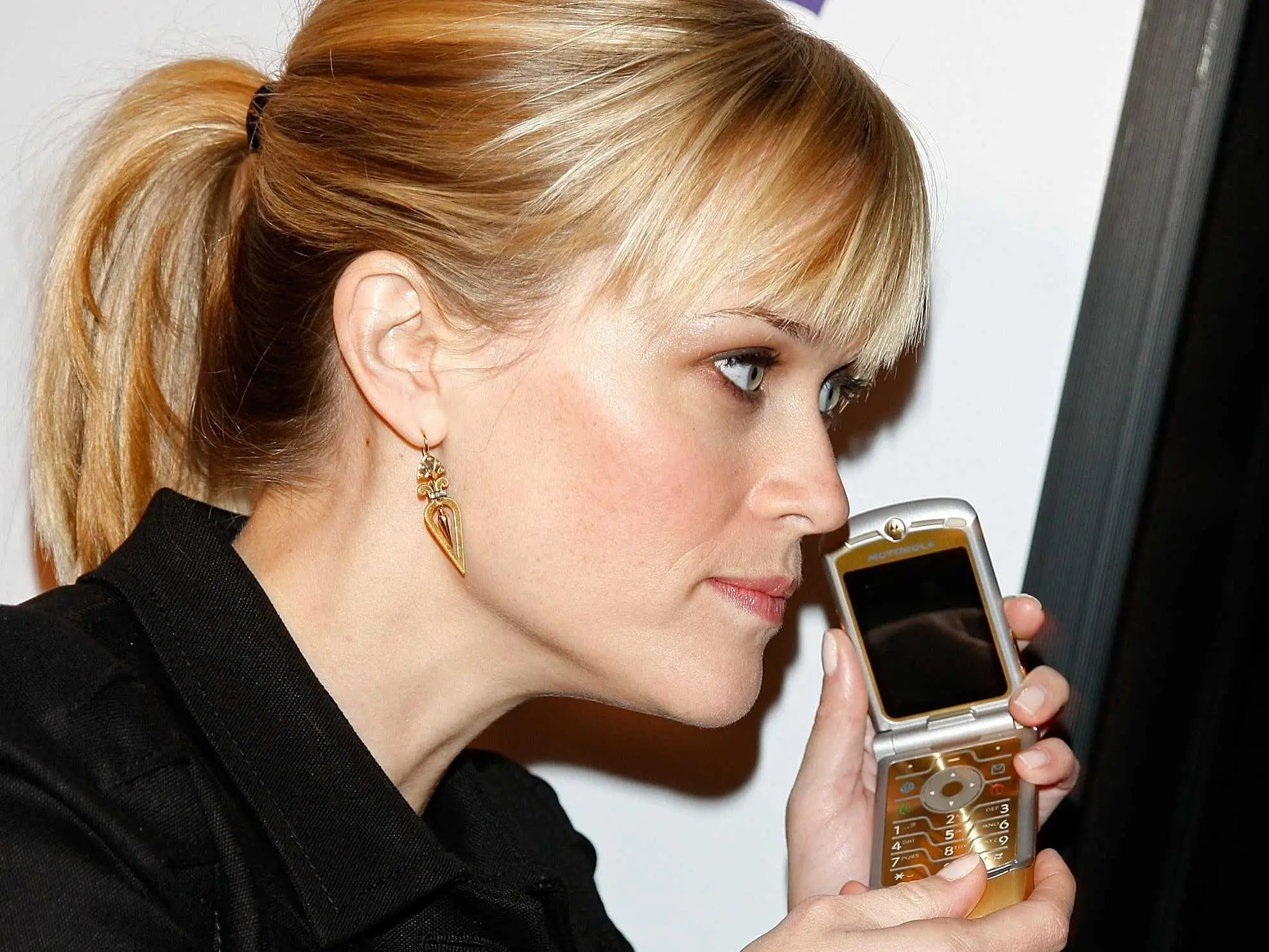 """February 2008: We can't exactly tell what Reese Witherspoon is doing with her phone at the premiere of """"Penelope"""" in LA, but we can tell she owns a gold-plated Motorola Razr."""
