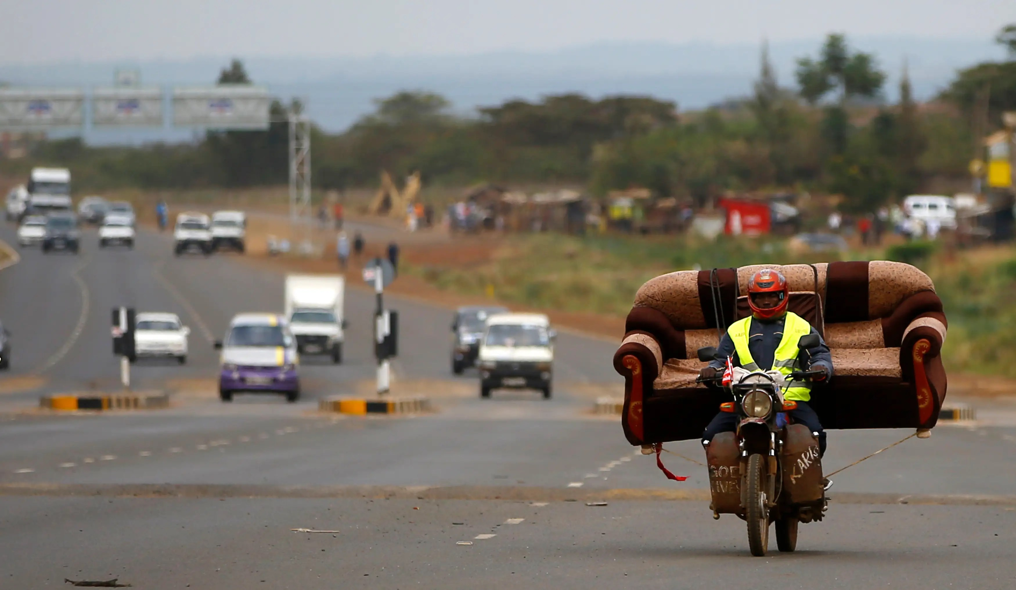 In Nairobi, Kenya, a man carries sofa on motorcycle.