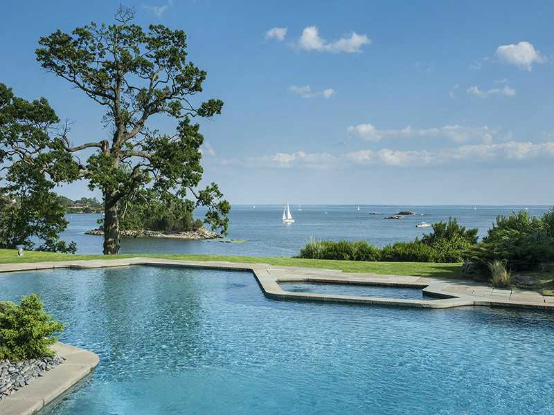 Facing the water is a 75-foot-long heated pool with hot tub.