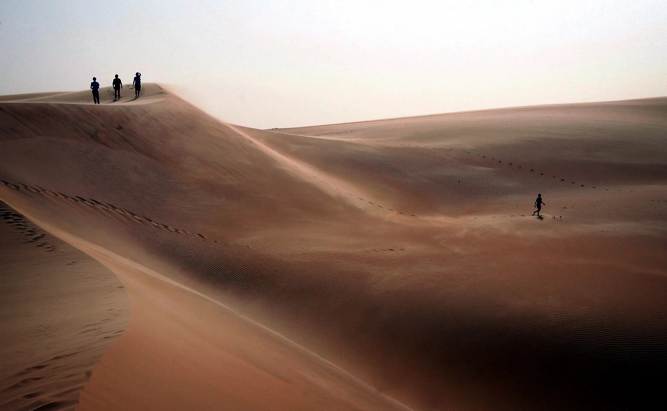 Tourists explore sand dunes in Africa's Mauritanian desert.