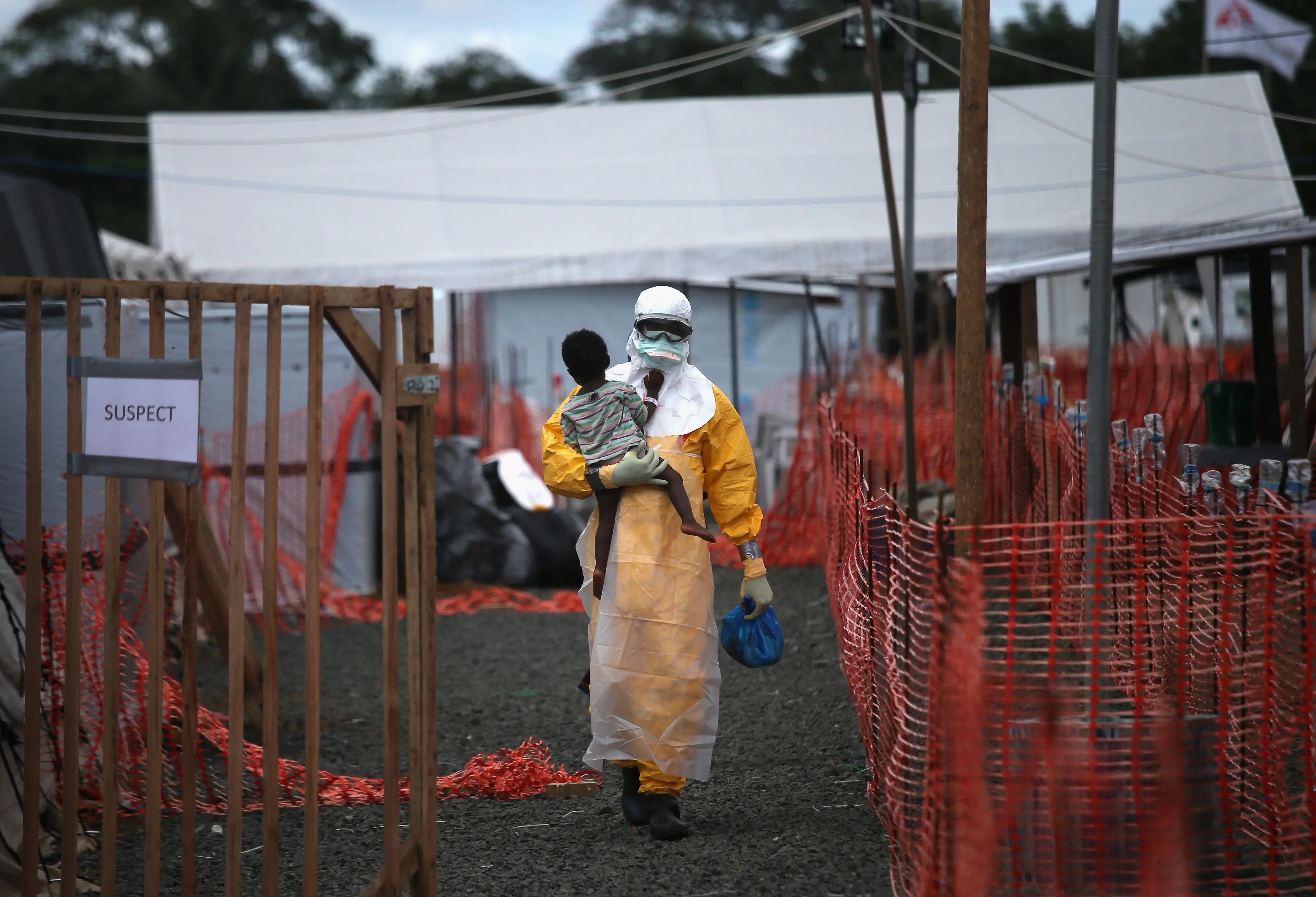 A Doctors Without Borders health worker in protective clothing carries a child suspected of having Ebola in the group's treatment center on Oct. 5 in Liberia.