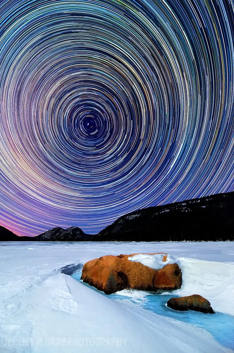 """Jeremy Gray shoots incredible images of Maine's night sky. Mesmerizing star trails paint the night sky along the frozen, snow-blanketed banks of Jordan Pond in Acadia National Park in this image Gray dubbed """"Celestial Winter."""""""
