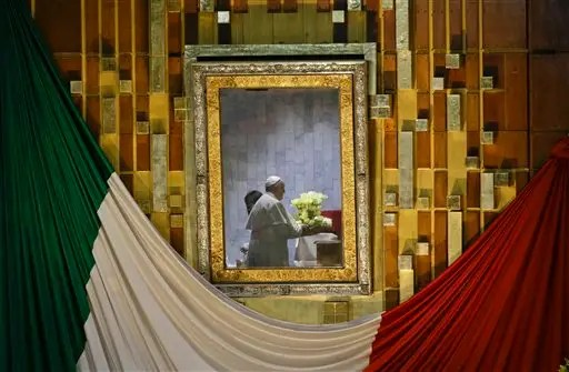 Pope Francis, seen on the other side of the framed glass that usually holds the image of the Virgin of Guadalupe, holds a flower bouquet as he prays to her inside a private room at the Basilica built in her honor, during Mass in Mexico City, Saturday, Feb. 13, 2016. The image in the frame was removed and placed inside the private room. The pontiff's five-day visit included a prayer before the Virgin of Guadalupe shrine, the largest and most important Marian shrine in the world and one that is particularly important to the first Latin American pope. (AP Photo/Gregorio Borgia)