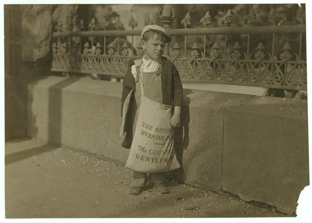 Freddie Kafer, a very immature little newsie selling Saturday Evening Posts and newspapers at the entrance to the State Capitol. He did not know his age, nor much of anything else. He was said to be 5 or 6 years old. Nearby, Hine found Jack who said he was 8 years old, and who was carrying a bag full of Saturday Evening Posts, which weighed nearly 1/2 of his own weight. The bag weighed 24 pounds, and he weighed only 55 pounds. He carried this bag for several blocks to the car. Said he was taking them home. Sacramento, California, May 1915.